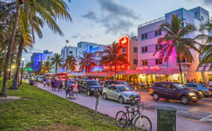 MIAMI USA - AUG 23 2014: people enjoy Palm trees and art deco hotels at Ocean Drive by night. The road is the main thoroughfare through South Beach in Miami USA.